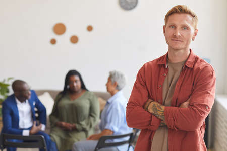 Waist up portrait of modern tattooed man posing confidently and looking at camera with people sitting in circle in background, support group concept, copy space 写真素材