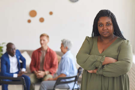 Waist up portrait of young African-American woman looking at camera with people sitting in circle in background, support group concept, copy space