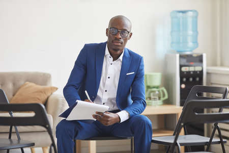 Portrait of elegant African-American man holding clipboard and looking at camera while sitting on chairs set in circle for support group meeting, male psychologist concept, copy space