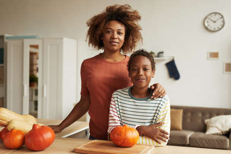 Beautiful African American woman and her teen son standing together at table with pumpkins for carving on it