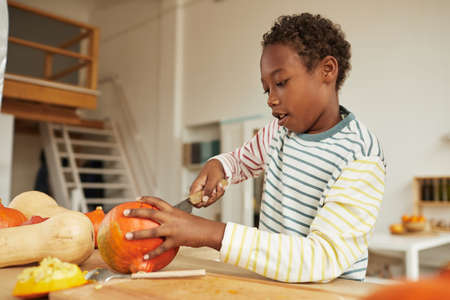 Portrait of preteen African American boy wearing casual outfit standing at table in kitchen carving pumpkin for Halloween