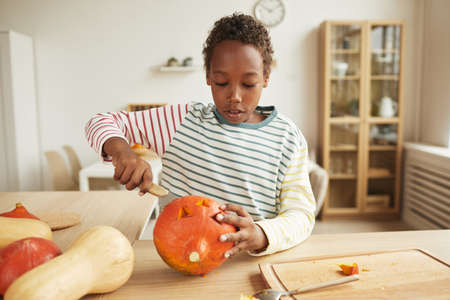 Modern African American boy wearing casual outfit standing at table at home carving face on pumpkin for Halloween party