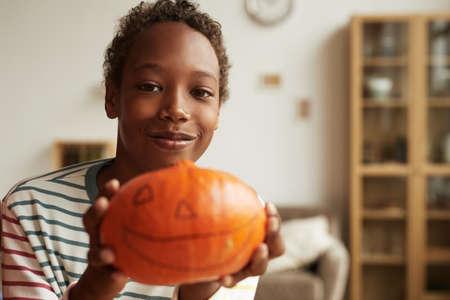 Medium close-up portrait of joyful African American kid holding ripe pumpkin with jack-o-lantern face drawn on it, copy space