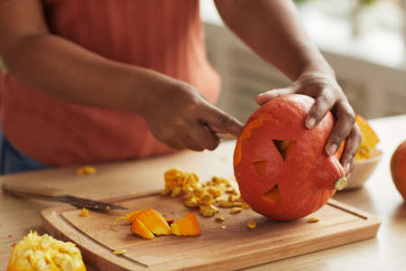 Unrecognizable modern young African American woman carving small pumpkin for Halloween decoration