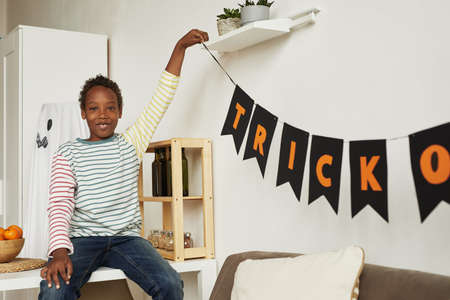 Cheerful African American boy wearing casual clothes decorating room for Halloween party, copy space