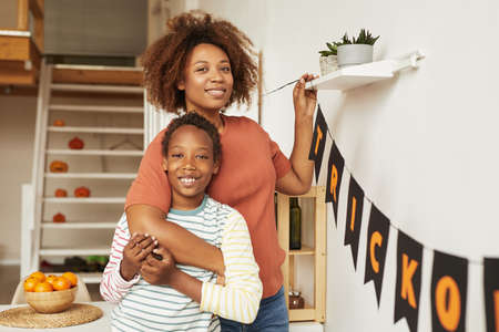 Horizontal medium portrait of happy young adult woman and her cheerful son smiling at camera while decorating room for Halloween