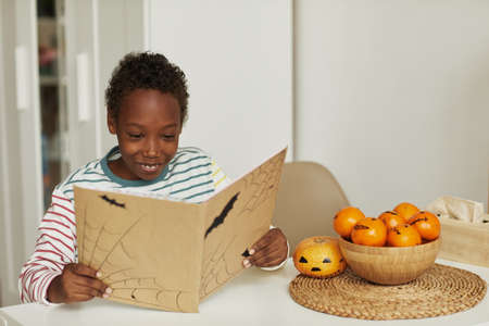 Happy African American boy sitting at table reading interesting Halloween story book, copy space 写真素材