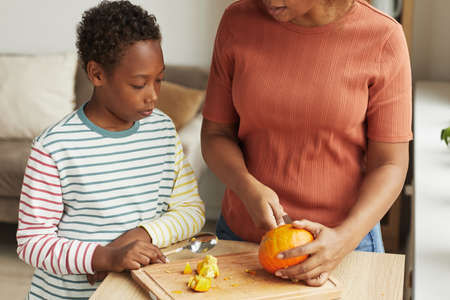 Unrecognizable woman standing at kitchen counter demonstrating her son how to carve pumpkin for Halloween 写真素材