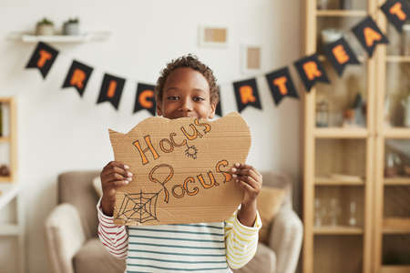 Modern joyful African American boy standing in living room decorated for Halloween holding cardboard with Hocus Pocus lettering 写真素材