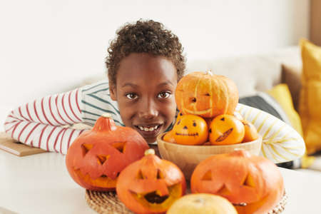 Portrait of cheerful African American boy posing on camera with pumpkins and tangerines he prepared for Halloween