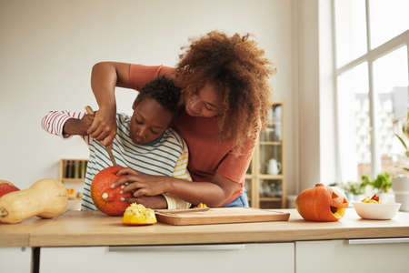Stylish African American woman spending time with her son standing at table carving pumpkin for Halloween with kitchen knife together 写真素材