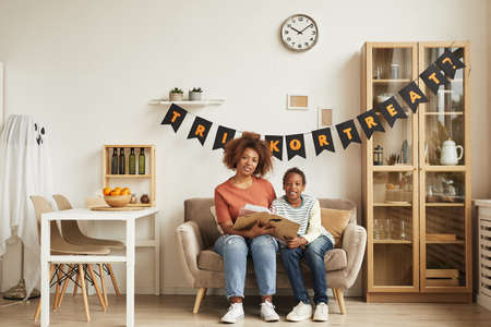 Modern young adult woman spending time with her son sitting together on sofa in living room decorated for Halloween and reading book, copy space 写真素材