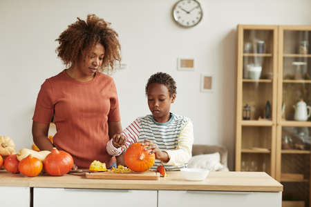 Young adult African American woman wearing casual outfit standing at table watching her child carving pumpkin