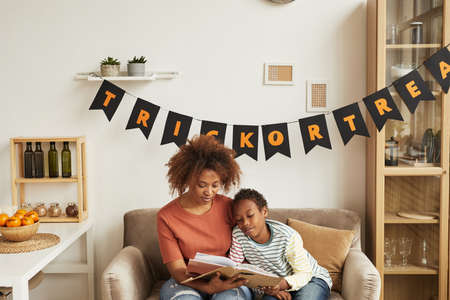 Modern African American mother sitting on sofa in living room with her young son reading spooky Halloween stories