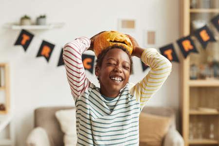 Playful African American boy having fun with Jack O Lantern pumpkin putting it on his head, medium portrait shot 写真素材