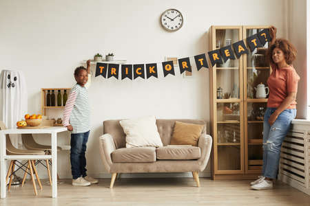 Modern young mother and her son hanging garland with Trick Or Treat lettering on wall for Halloween party