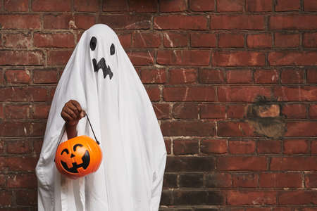 Unrecognizable kid dressed up as ghost wearing white fabric holding jack o lantern basket for sweets standing against brick wall 写真素材