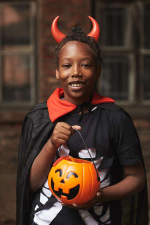Vertical medium portrait of happy African American boy dressed up as devil with red horns holding basket full of candies after trick-or-treating