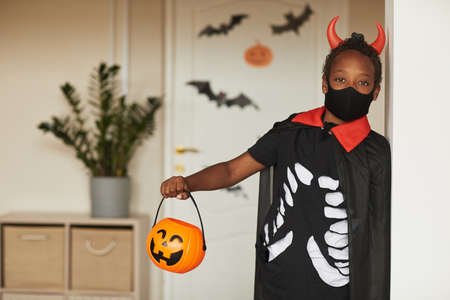 Portrait of cute African American boy wearing spooky devil costume with red horns and mask holding jack o lantern basket for candies looking at camera 写真素材