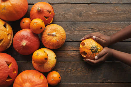 Directly from above view flat lay shot of carved pumpkins and tangerines with jack o lantern faces and womans hands holding one pumpkin for Halloween on dark wooden table background... 写真素材