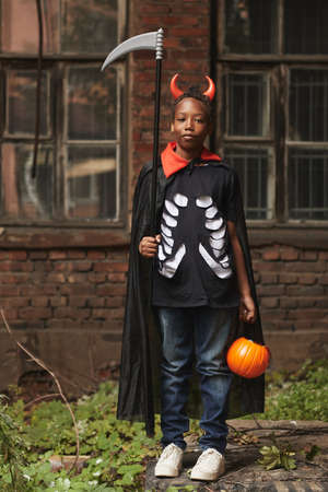 Vertical full shot portrait of cool African American boy dressed up as devil with red horns and scythe standing against old building looking at camera