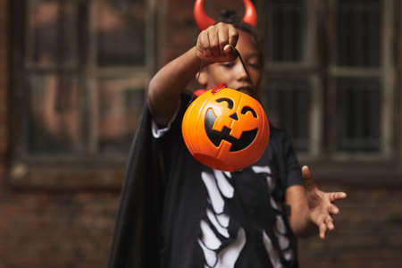 Young boy wearing devil costume demonstrating jack o lantern basket for candies while trick-or-treating