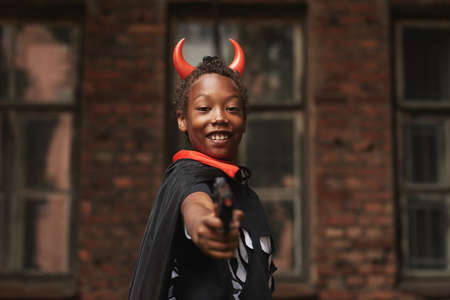 Portrait of joyful preteen boy dressed up as devil with red horns for Halloween party standing against old building shooting at camera with toy gun