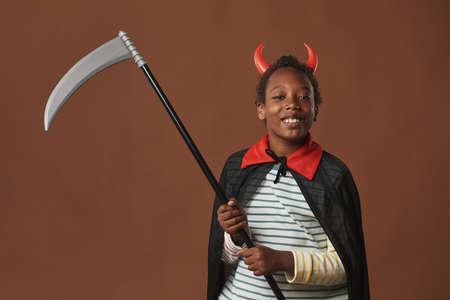 Studio portrait of cheerful African American preteen boy wearing red horns on head and costume mantle holding scythe looking at camera smiling, brown background 写真素材