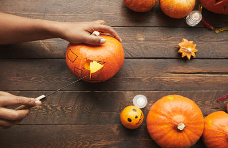 Horizontal from above view shot of hands carving ripe pumpkin for Hallowing party with kitchen knife on dark brown wooden table 写真素材