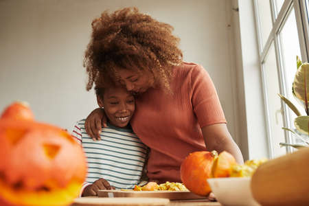 Loving mother hugging her cheerful son while carving ripe pumpkins for Halloween party together