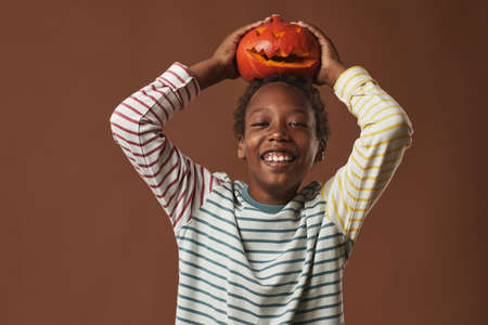Cheerful African American boy wearing striped long-sleeve shirt holding Jack O Lantern on his head smiling at camera, studio portrait