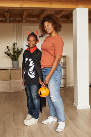 Vertical full shot of modern woman and her son wearing little devil costume standing together looking at camera