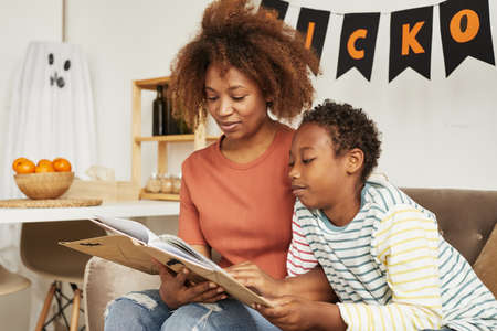 Beautiful African American woman sitting on sofa in living room with her preteen son reading interesting Halloween stories book