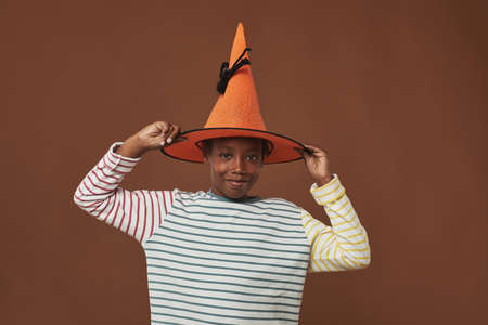 Studio portrait of cheerful young boy standing against brown wall background trying on funny orange wizard hat looking at camera