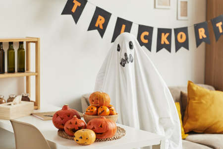 Unrecognizable child having fun hiding in ghost costume in living room decorated for Halloween party 写真素材