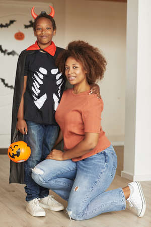Vertical full shot of beautiful woman and her preteen son wearing little devil costume for Halloween looking at camera 写真素材