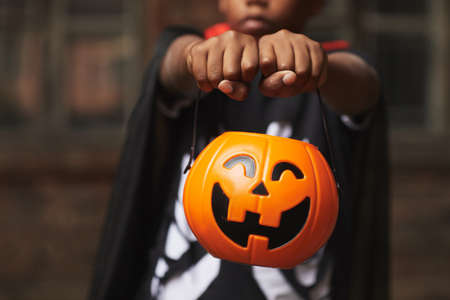 Unrecognizable boy wearing modern Halloween costume demonstrating plastic Jack O Lantern basket for candies while trick-or-treating