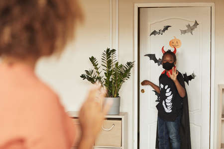 Over-the-shoulder shot of young mother seeing off her little son who is wearing devil Halloween costume going out for trick-or-treating with friends.