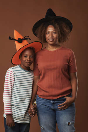Vertical medium long studio portrait of modern young woman and her cute son wearing magician hats standing against brown wall background 写真素材