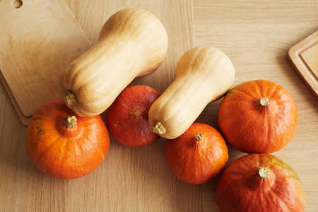 Top-down shot of beautiful fresh ripe pumpkins and cutting boards lying on light brown wooden table 写真素材