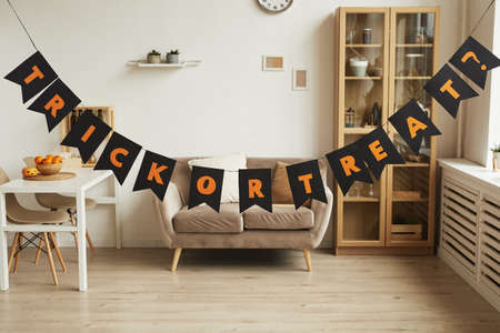 Horizontal no people shot of modern room interior with Trick or Treat lettering garland in it prepared for Halloween party 写真素材