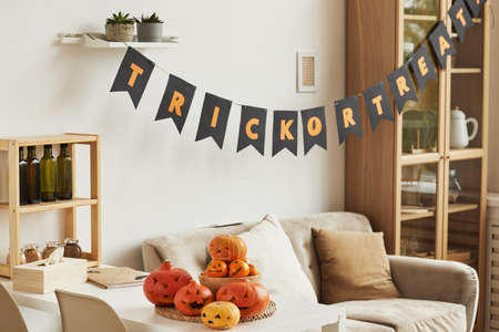 Horizontal no people shot of modern room interior with Trick or Treat lettering garland and carved pumpkins prepared for Halloween party