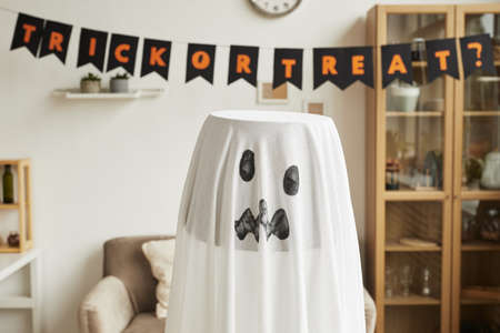 Horizontal close-up shot of lamp decorated with white fabric with ghost face painted on it for Halloween