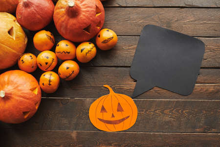 Horizontal top-down shot of carved pumpkins, tangerines paper Jack-O-Lantern with black quote box lying on dark brown wooden table 写真素材