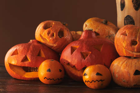 Group of spooky pumpkins, gourds and tangerines carved and painted for Halloween party decoration against brown wall background, studio shot