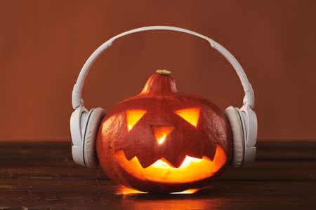 Close-up studio shot of modern Jack O Lantern pumpkin with candle inside wearing white headphones, brown background