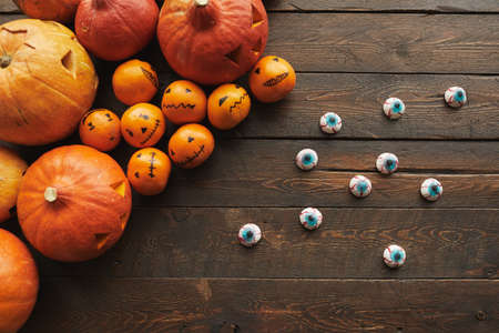 Top-down flat lay composition of carved pumpkins, tangerines with jack o lantern faces and scary eyeball candies lying on wooden table 写真素材