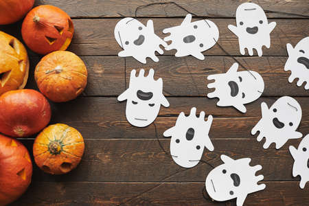 From above flat lay shot of carved pumpkins and cute paper ghosts for Halloween lying on dark brown wooden table surface 写真素材