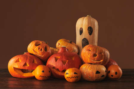 Group of pumpkins, gourds and tangerines carved and painted for Halloween party decoration against brown background