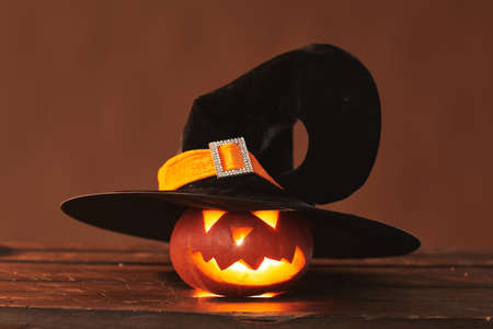 Close-up studio shot of cute Jack O Lantern wearing black witch hat with candle glowing inside of it, brown background